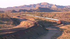 A freight train moves across the desert from a high angle. Stock Footage