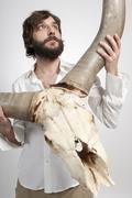 Stock Photo of Man holding buffalo skull