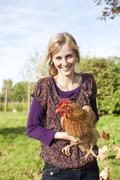 Germany, Saxony, Young woman with hens, portrait, smiling Stock Photos