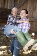 Germany, Saxony, Man carrying woman at the farm, smiling - stock photo