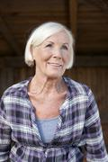 Germany, Saxony, Senior woman at the farm, smiling - stock photo