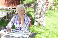 Germany, Saxony, Senior woman with newspaper at the farm - stock photo