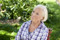 Germany, Saxony, Senior woman relaxing at the farm - stock photo