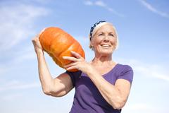 Germany, Saxony, Senior woman carrying pumpkin on shoulder Stock Photos