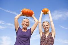 Germany, Saxony, Women holding pumpkin, smiling - stock photo