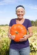 Germany, Saxony, Senior woman carrying pumpkin, smiling, portrait - stock photo