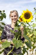 Germany, Saxony, Young woman with sunflower, smiling Stock Photos