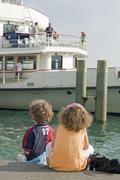 Germany, Baden-Wurttemberg, Lake Constance, Children watching pleasure boat - stock photo