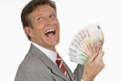Businessman holding Euro banknotes, side view, portrait, close-up - stock photo