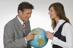 Businessman and Businesswoman holding globe, side view, smiling, portrait Stock Photos