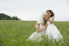 Flower girl (4-5) whispering to bride on meadow Stock Photos