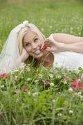 Stock Photo of Bride lying on meadow, smiling, looking away.