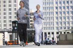 Germany, Berlin, Young couple jogging together Stock Photos