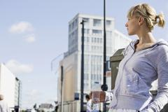 Germany, Berlin, Young woman holding water bottle, looking away, portrait - stock photo
