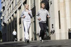 Germany, Berlin, Young couple jogging together - stock photo