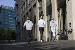 Germany, Berlin, Three friends jogging together - stock photo