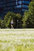 Germany, Berlin, Young woman jogging, rear view - stock photo
