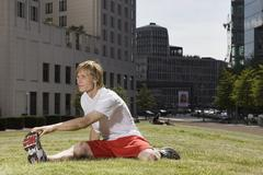 Stock Photo of Germany, Berlin, Young man stretching on lawn