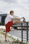 Stock Photo of Germany, Berlin, Young man stretching leg on railing