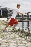 Germany, Berlin, Young man stretching on railing - stock photo