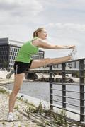 Germany, Berlin, Young woman stretching leg on railing, side view - stock photo