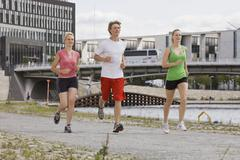 Germany, Berlin, Three friends jogging in the city Stock Photos