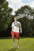 Germany, Berlin, Young man on lawn playing with soccer ball Stock Photos