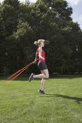 Germany, Berlin, Young woman jumping rope in park - stock photo