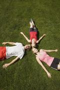 Germany, Berlin, Three persons lying on lawn, elevated view - stock photo