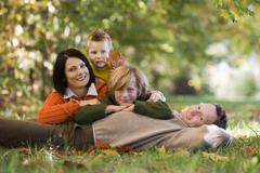 Stock Photo of parents with two children (6-11) lying in meadow, smiling