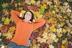 woman lying on autumn leaves, elevated view - stock photo