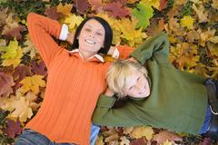 mother and son (8-11) lying on autumn leaves, elevated view, portrait - stock photo
