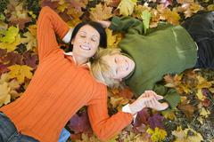 Mother and son lying on autumn leaves, elevated view Stock Photos