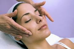 Stock Photo of young woman receiving facial massage, eyes closed, close-up
