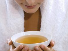 young woman holding tea bowl, mid section, close-up - stock photo