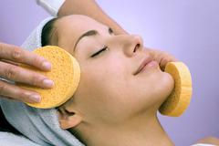 Stock Photo of young woman receiving facial massage, close-up