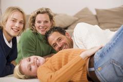 family lying on floor in living room - stock photo