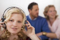 teenage girl wearing head phones, parents in background - stock photo