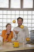 Mature couple in kitchen, man juggling with grapefruits Stock Photos