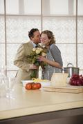 Mature couple in kitchen with flower bouquet Stock Photos