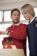 Stock Photo of father and teenage son (16-17) in kitchen, father pointing on watch, low angle