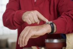 Stock Photo of man pointing on wristwatch