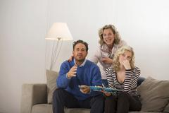 Parents with daughter sitting on sofa Stock Photos