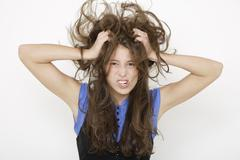Stock Photo of Young woman (16-17) tearing her hair