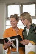 Mother and son in kitchen, reading school report Stock Photos