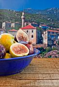 bowl of fresh figs on rustic wooden table against village background - stock photo