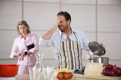 man cooking, woman standing in background - stock photo