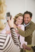 daughter photographing parents with mobile phone - stock photo