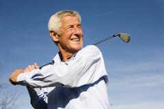 Stock Photo of senior man swinging golf club, smiling, close-up