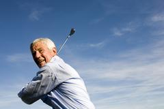 Stock Photo of senior adult man holding golf club